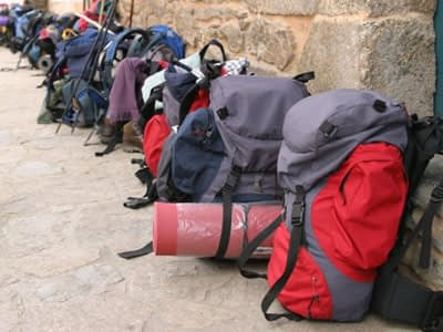 Backpacks lined against a wall waiting for bag transport